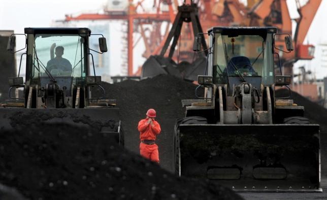7月7日、中国共産党機関紙「人民日報」系の環球時報は中国と北朝鮮の貿易が第1・四半期に増加したのは「予想外」であり、長期の減少トレンドを覆い隠しているとの社説を掲載した。写真は遼寧省の丹東港で北朝鮮から輸入した石炭の積み下ろしを行う作業員。2010年12月撮影(2017年 ロイター)