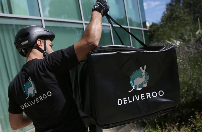 A Deliveroo worker loads his bicycle after making a delivery in London, Britain August 15, 2016. Neil Hall