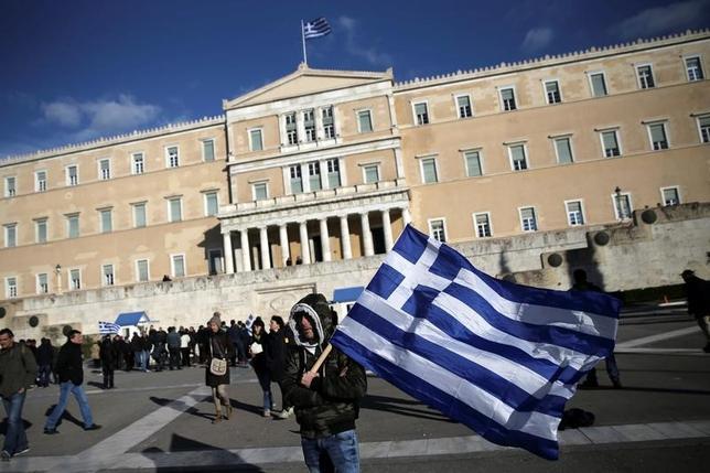 7月11日、ギリシャが向こう数週間以内に市場から資金を調達するとの見方が市場で高まっていることが分かった。実際に調達すれば2014年以来となる。写真はギリシャ議会前で同国国旗を抱えたデモ参加者。2月14日撮影。(2017年 ロイター/Alkis Konstantinidis)