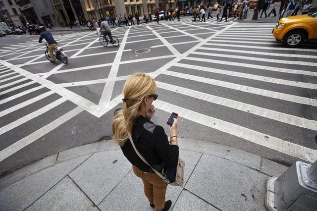 A woman uses her Apple iPhone while waiting to cross 5th Avenue in New York, September 20, 2012.  Apple's iPhone 5 goes on sale tomorrow as Apple works to increase it's market share in the mobile phone market. REUTERS/Lucas Jackson
