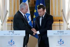 الرئيس الفرنسي إيمانويل ماكرون (إلى اليمين) يصافح رئيس وزراء إسرائيل بنيامين نتنياهو خللال مؤتمر صحفي في باريس يوم الأحد. تصوير: ستيفان مايه - رويترز