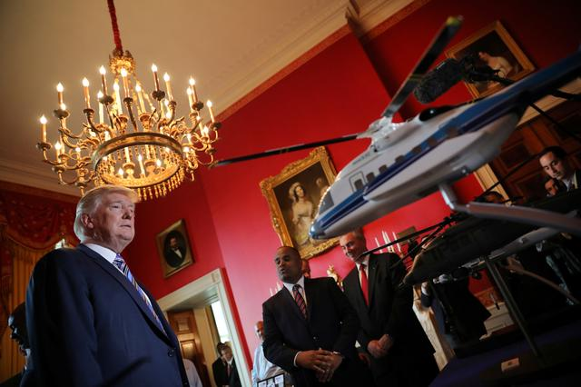 President Donald Trump looks at Sikorsky helicopters miniature models. ''Your drivers are very good,'' Trump said to a representative of Ping, the Arizona-based maker of golf clubs, noting that he had golfed with British pro golfer Lee Westwood, who is a fan. He discussed sales of Sikorsky helicopters - ''I have three of them!'' he said, lifted horseshoes made with Nucor Corp steel, and strolled past vacuum-sealed Omaha steaks.REUTERS/Carlos Barria