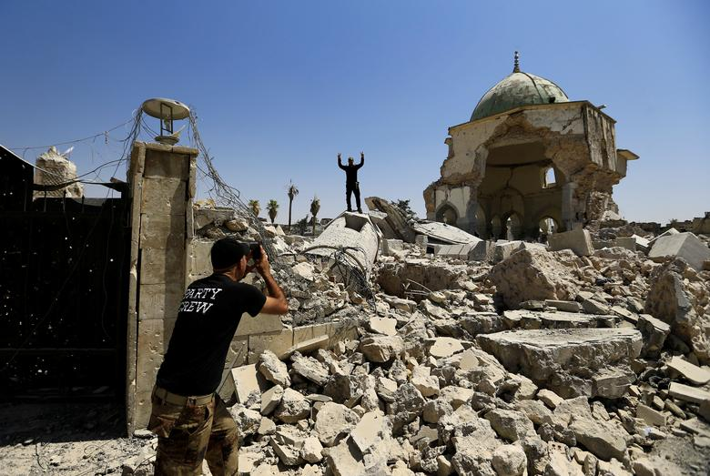 Members of the Counter Terrorism Service (CTS) take a selfie in front of the ruins of Grand al-Nuri Mosque in the Old City, July 20, 2017. REUTERS/Thaier Al-Sudani