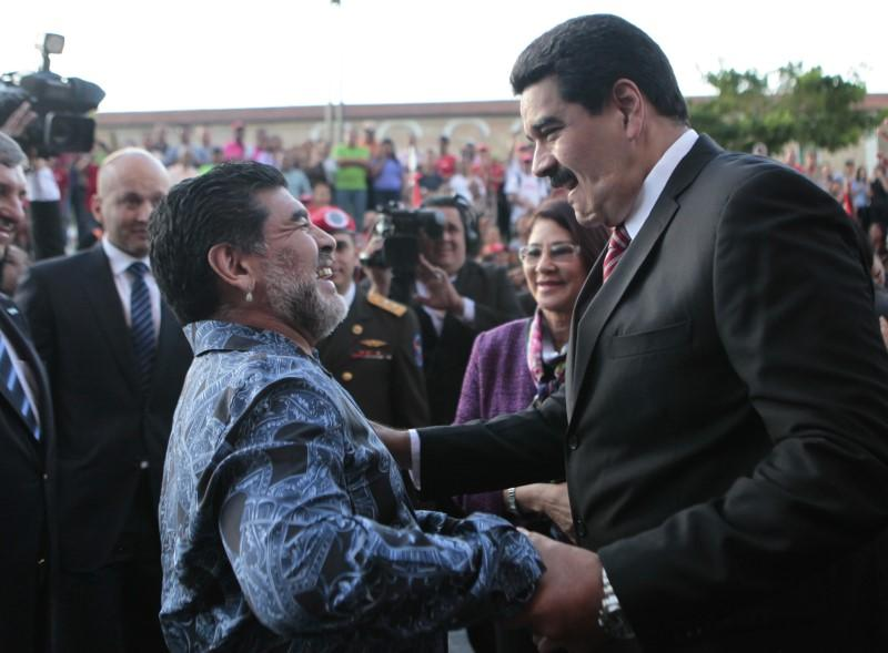 Venezuela's President Nicolas Maduro (R) greets former Argentine soccer star Diego Maradona during a ceremony at the national pantheon in Caracas in this ...