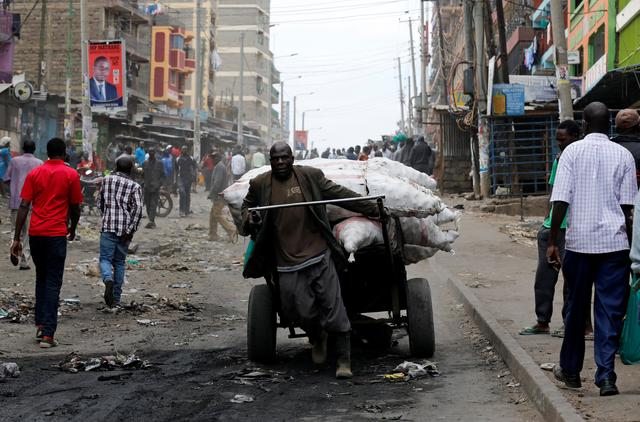 A man pulls a barrow through the streets of Mathare, Nairobi, Kenya, August 13, 2017. REUTERS/Thomas Mukoya