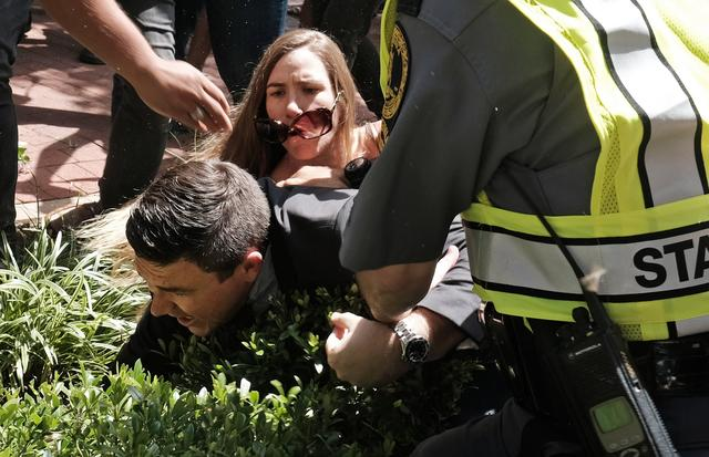 Unite The Right rally organizer Jason Kessler is helped by police after being tackled by a woman after he attempted to speak at a press conference in front of Charlottesville City Hall in Charlottesville, Virginia,  August 13, 2017. REUTERS/Justin Ide