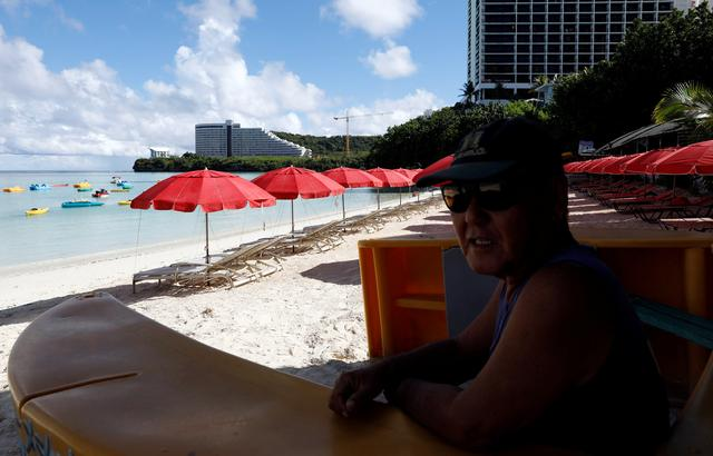 A resort worker waits for customers along a beach in Tumon Bay on the island of Guam, a U.S. Pacific Territory, August 14, 2017.  REUTERS/Erik De Castro