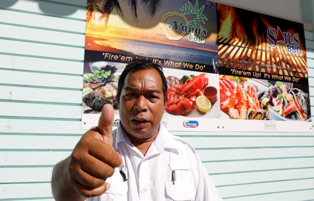A resort park attendant gestures a thumbs up sign as he poses outside a restaurant in Tumon tourist district on the island of Guam, a U.S. Pacific Territory, August 14, 2017.  REUTERS/Erik De Castro