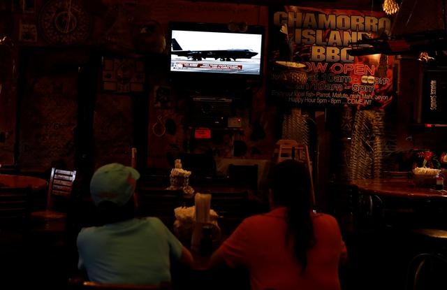 Local residents watch the news on the North Korea crisis, at a restaurant, on the island of Guam, a U.S. Pacific Territory, August 14, 2017. REUTERS/Erik De Castro
