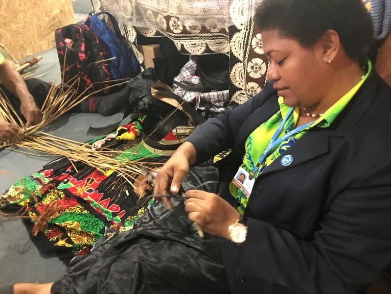 A Fijian craftswoman works at a pavilion during the COP23 UN Climate Change Conference 2017, hosted by Fiji but held in Bonn, Germany November 9, 2017. Picture taken November 9, 2017. Alister Doyle