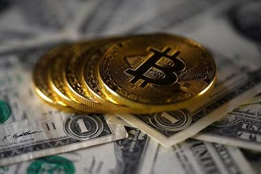 FILE PHOTO - Bitcoin (virtual currency) coins placed on Dollar banknotes...