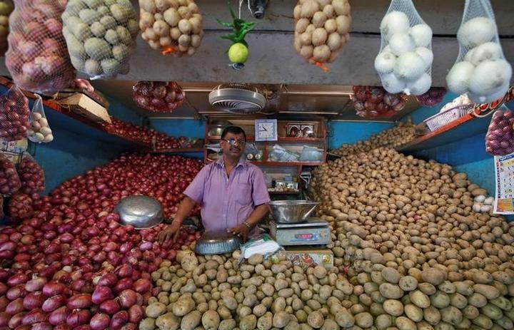 FILE PHOTO: A vendor waits for customers at his vegetable stall at a...
