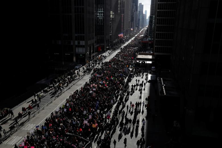 People walk down Sixth Avenue as they participate in the Women's March in Manhattan. REUTERS/Andrew Kelly