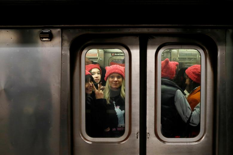 A group of people wearing pussyhats ride the subway at 42nd Street as they head toward the Women's March in Manhattan. REUTERS/Andrew Kelly