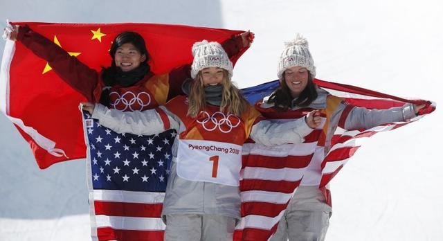 Snowboarding - Pyeongchang 2018 Winter Olympics - Women's Halfpipe Finals - Phoenix Snow Park - Pyeongchang, South Korea - February 13, 2018 - Gold medallist Chloe Kim of the U.S., flanked by silver medallist Liu Jiayu of China and bronze medallist Arielle Gold of the U.S., poses with their national flags during flower ceremony. REUTERS/Issei Kato