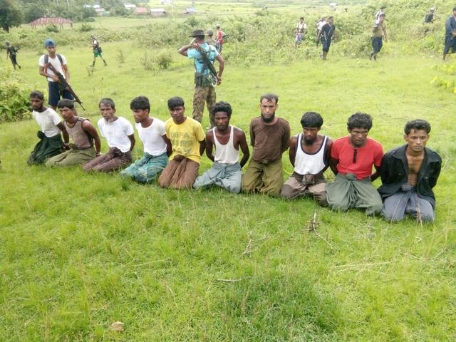 FILE PHOTO: Ten Rohingya Muslim men with their hands bound kneel as members of the Myanmar security forces stand guard in Inn Din village September 2, 2017.    Handout via REUTERS