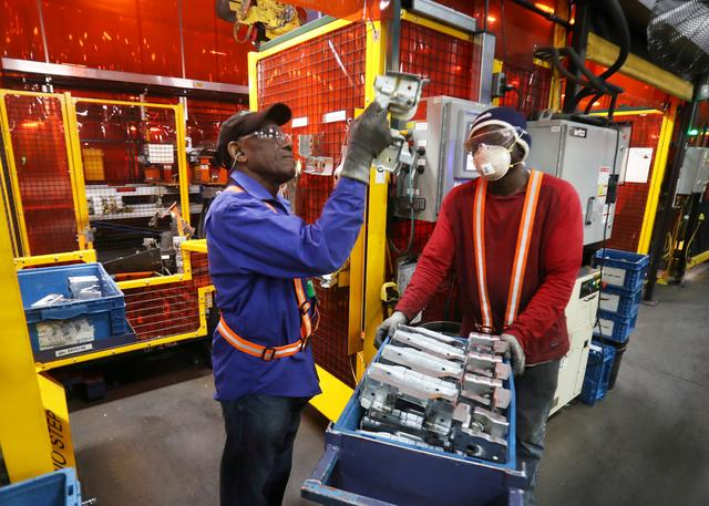 FILE PHOTO:    Workers examine parts for welding next to robot bay at Alfield Industries, a subsidiary of Martinrea, one of three global auto parts makers in Canada, in Vaughan, Ontario, Canada April 28, 2017. REUTERS/Fred Thornhill/File Photo