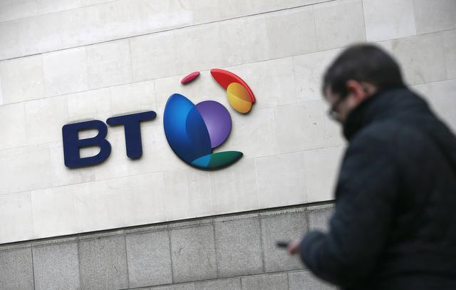 FILE PHOTO: A passer-by talks on their phone as she passes a branded sign displayed outside of a BT building in London, Britain January 27, 2017. REUTERS/Neil Hall/File Photo
