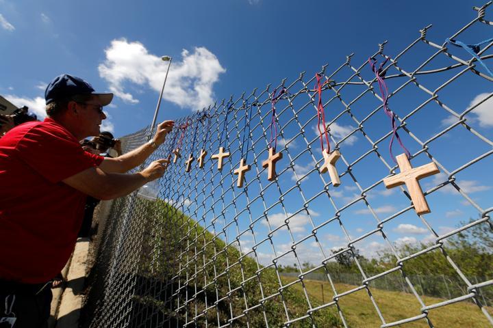 Chaplain places crosses for the victims of the Marjory Stoneman Douglas...
