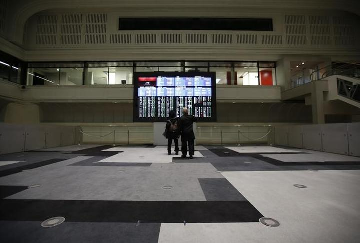 Visitors looks at an electronic board showing the Japan's Nikkei average at...
