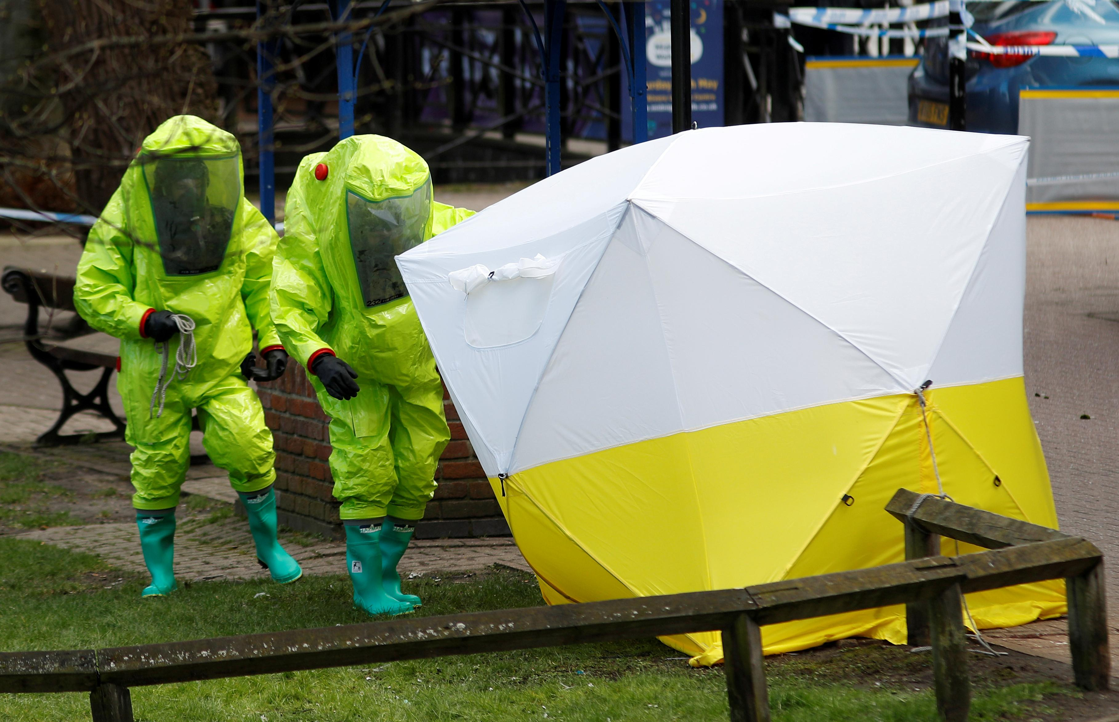 British officials in protective suits reposition the forensic tent, covering the bench where Sergei Skripal and his daughter Yulia were found unconscious in Salisbury, March 8, 2018. Peter Nicholls