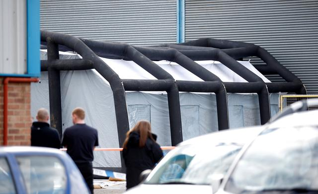 Police officers erect screens at a car recovery depot in Norton Enterprise Park, where Sergei Skripal's car was originally transported, in Salisbury, Britain, March 13, 2018. REUTERS/Henry Nicholls