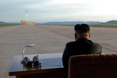 North Korean leader Kim Jong Un watches the launch of a Hwasong-12 missile...