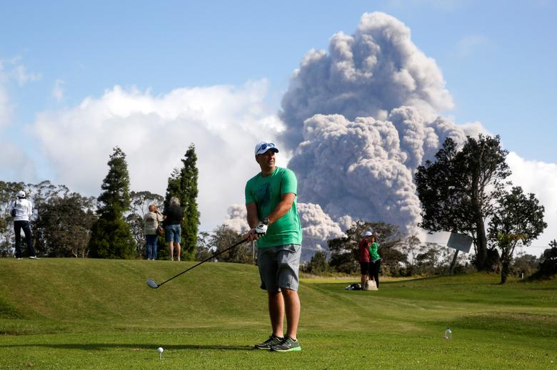 Sean Bezecny, 46, of Houston, Texas, takes a golf swing as ash erupts from the Halemaumau Crater. REUTERS/Terray Sylvester