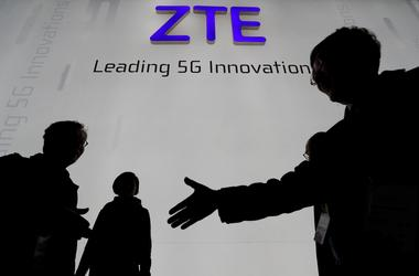 FILE PHOTO - Visitors pass in front of the ZTE booth at the Mobile World...