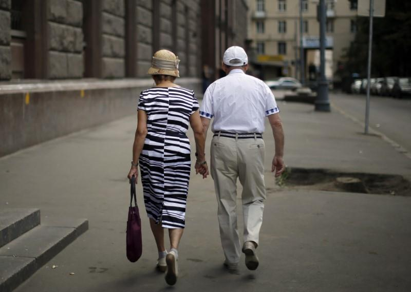 A couple walks down the street in the Tverskaya district of Moscow August 17, 2013.  Lucy Nicholson