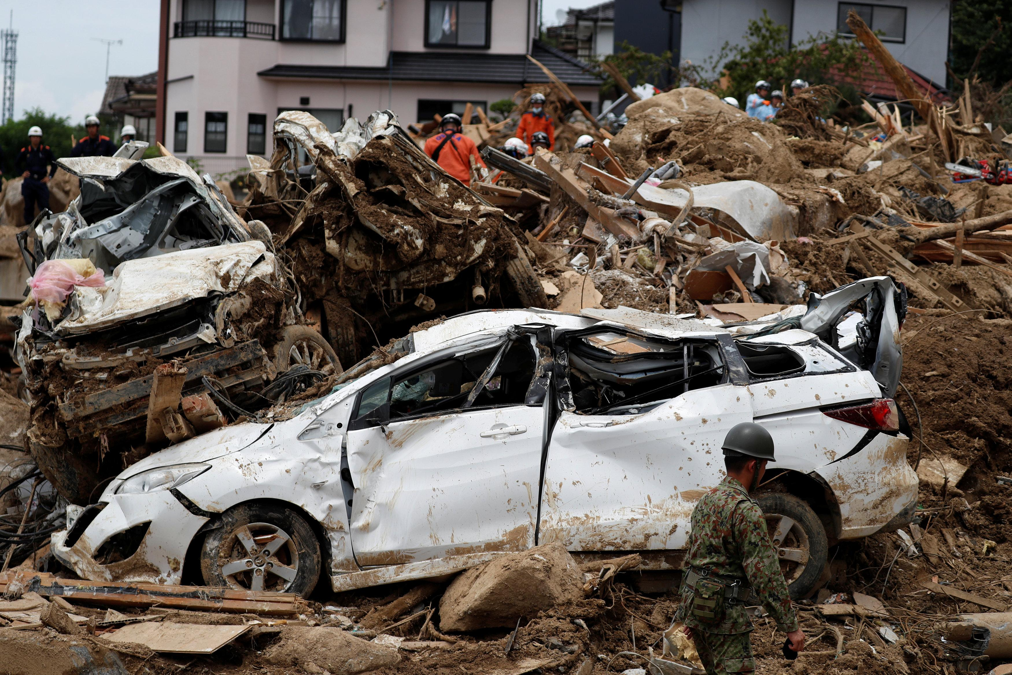 Rescue workers conduct search and rescue operations at a landslide site caused by heavy rain in Kumano Town, Hiroshima Prefecture, western Japan, July 11, 2018. Issei Kato