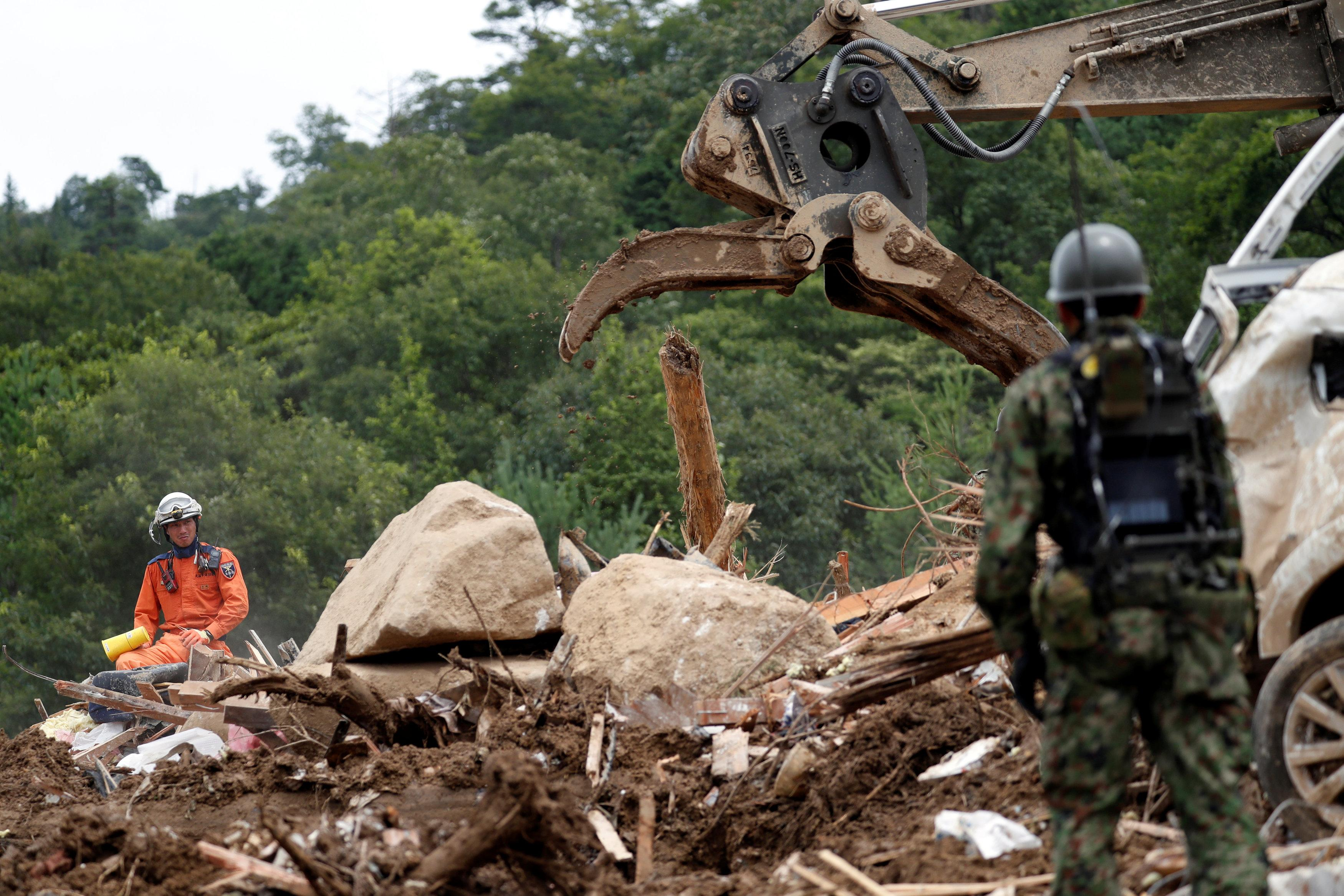 Rescue workers and Japan Self-Defense Force soldiers search for missing people at a landslide site caused by a heavy rain in Kumano Town, Hiroshima Prefecture, western Japan, July 11, 2018. Issei Kato