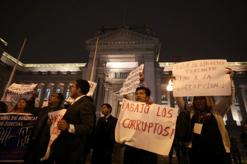People hold signs during a protest against corruption, following an influence-peddling scandal that has shaken the country's justice system, in Lima, Peru July 19, 2018.  Mariana Bazo