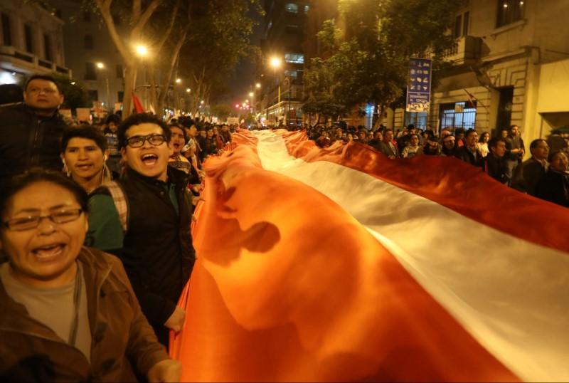 People hold a Peruvian flag during a protest against corruption, following an influence-peddling scandal that has shaken the country's justice system, in Lima, Peru July 19, 2018.  Mariana Bazo