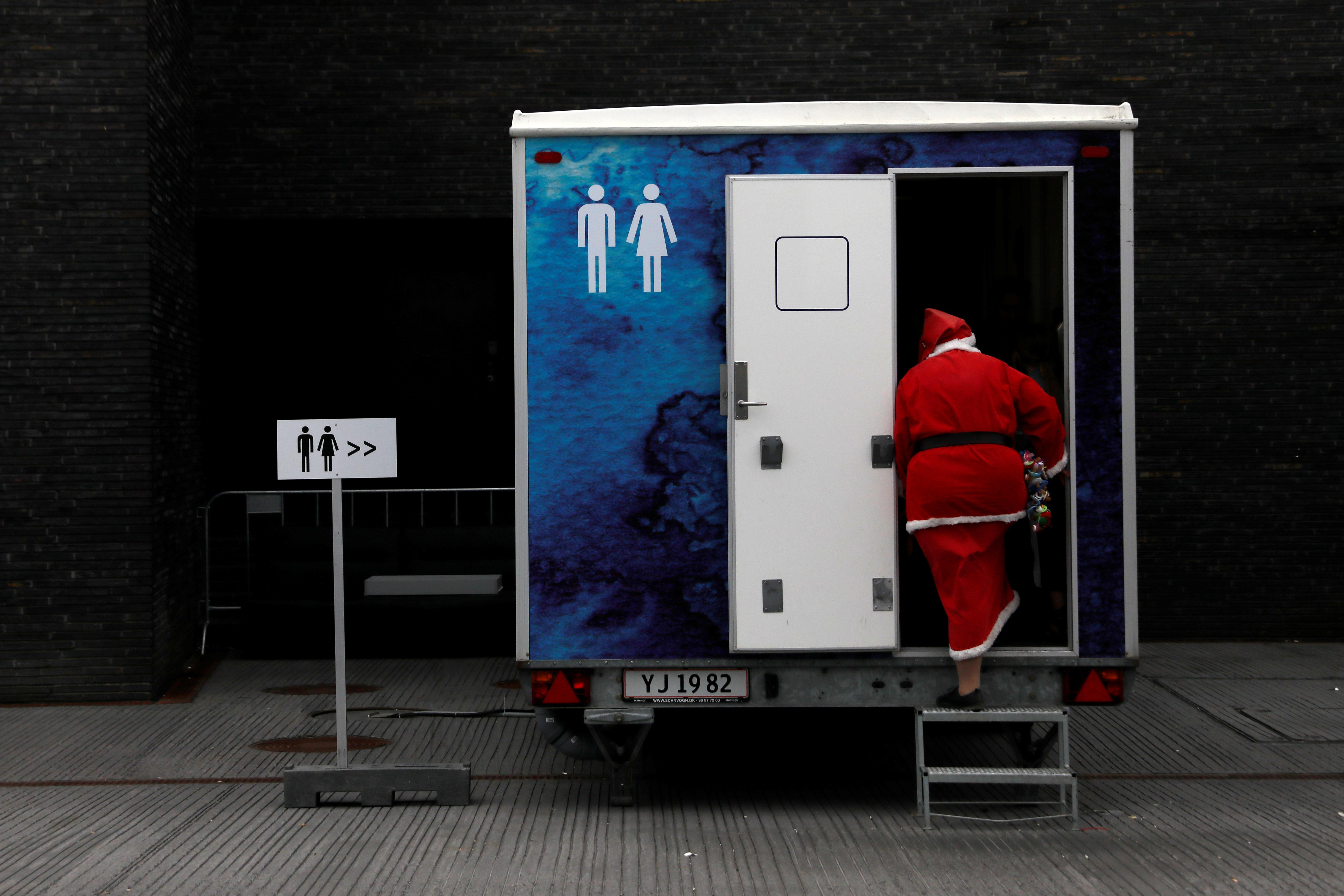 A person dressed as Santa Claus uses a restroom during the World Santa Claus Congress, an annual event held every summer in Copenhagen, Denmark, July 23, 2018.  Andrew Kelly