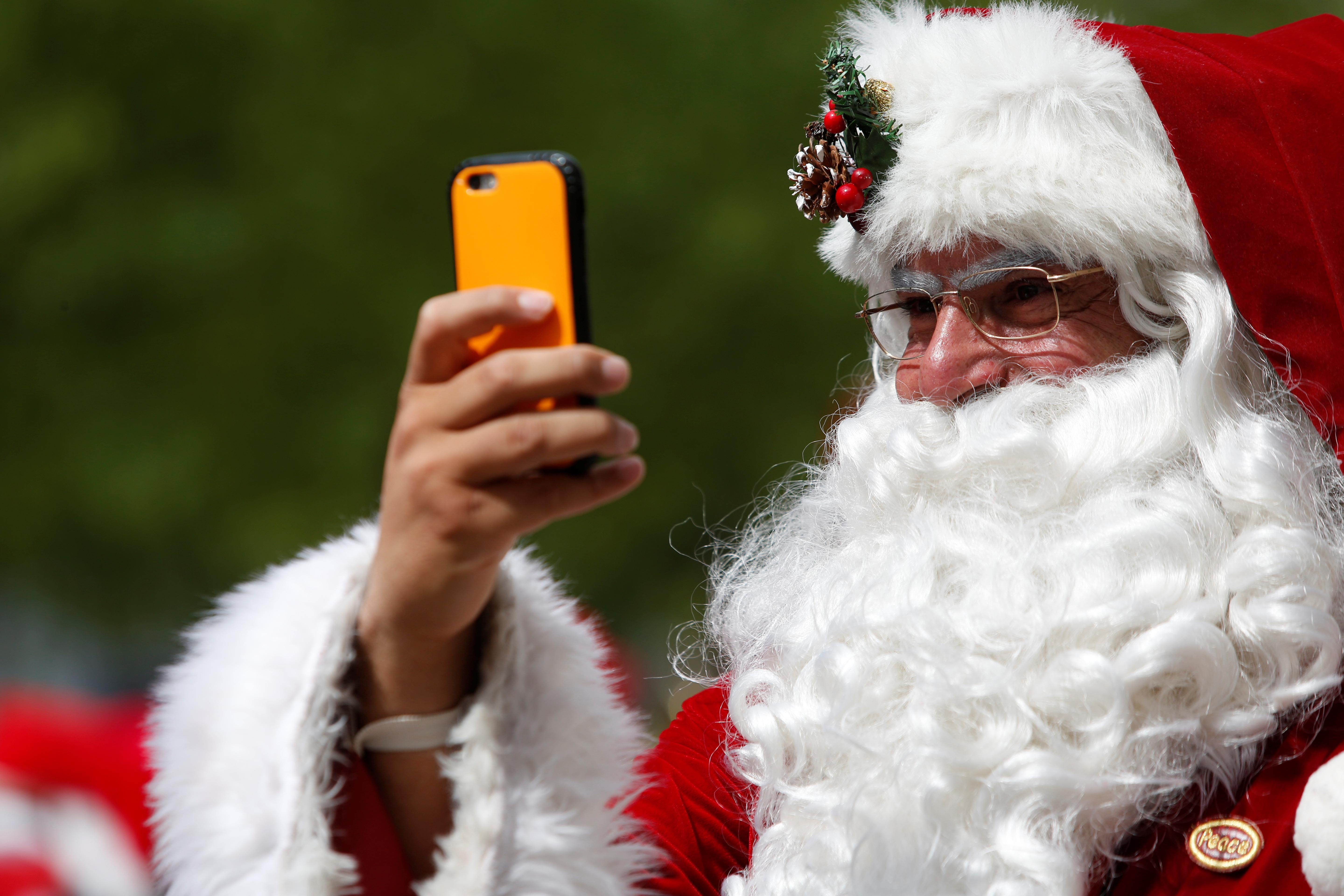 A man dressed as Santa Claus records on his cellphone as he takes part in the World Santa Claus Congress, an annual event held every summer in Copenhagen, Denmark, July 23, 2018.  Andrew Kelly