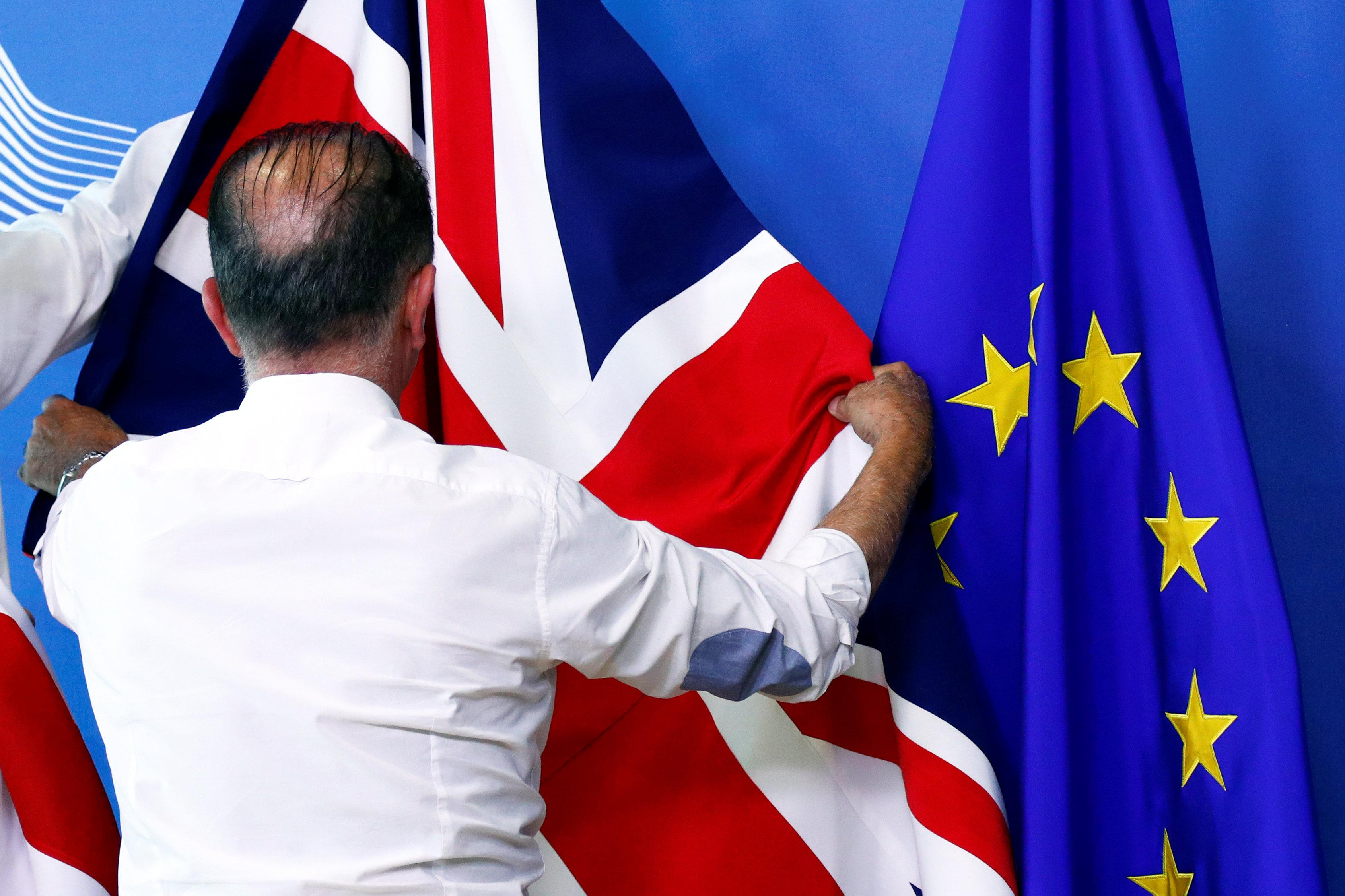 An official adjusts a Union Jack flag next to the European Union flag, ahead of a meeting between Britain's Secretary of State for Exiting the European Union, Dominic Raab, and European Union's chief Brexit negotiator, Michel Barnier, at the EU Commission headquarters in Brussels, Belgium July 19, 2018.   Francois Lenoir