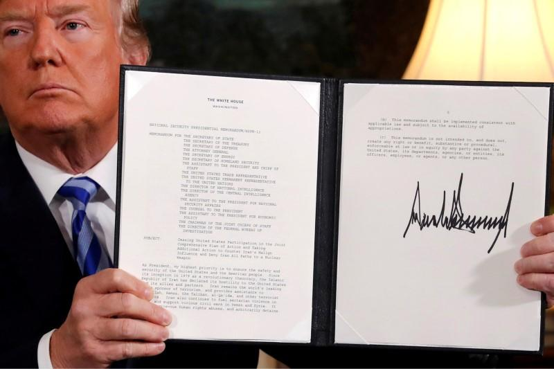 U.S. President Donald Trump holds up a proclamation declaring his intention to withdraw from the Iran nuclear agreement after signing it at the White House, May 8, 2018.  Jonathan Ernst