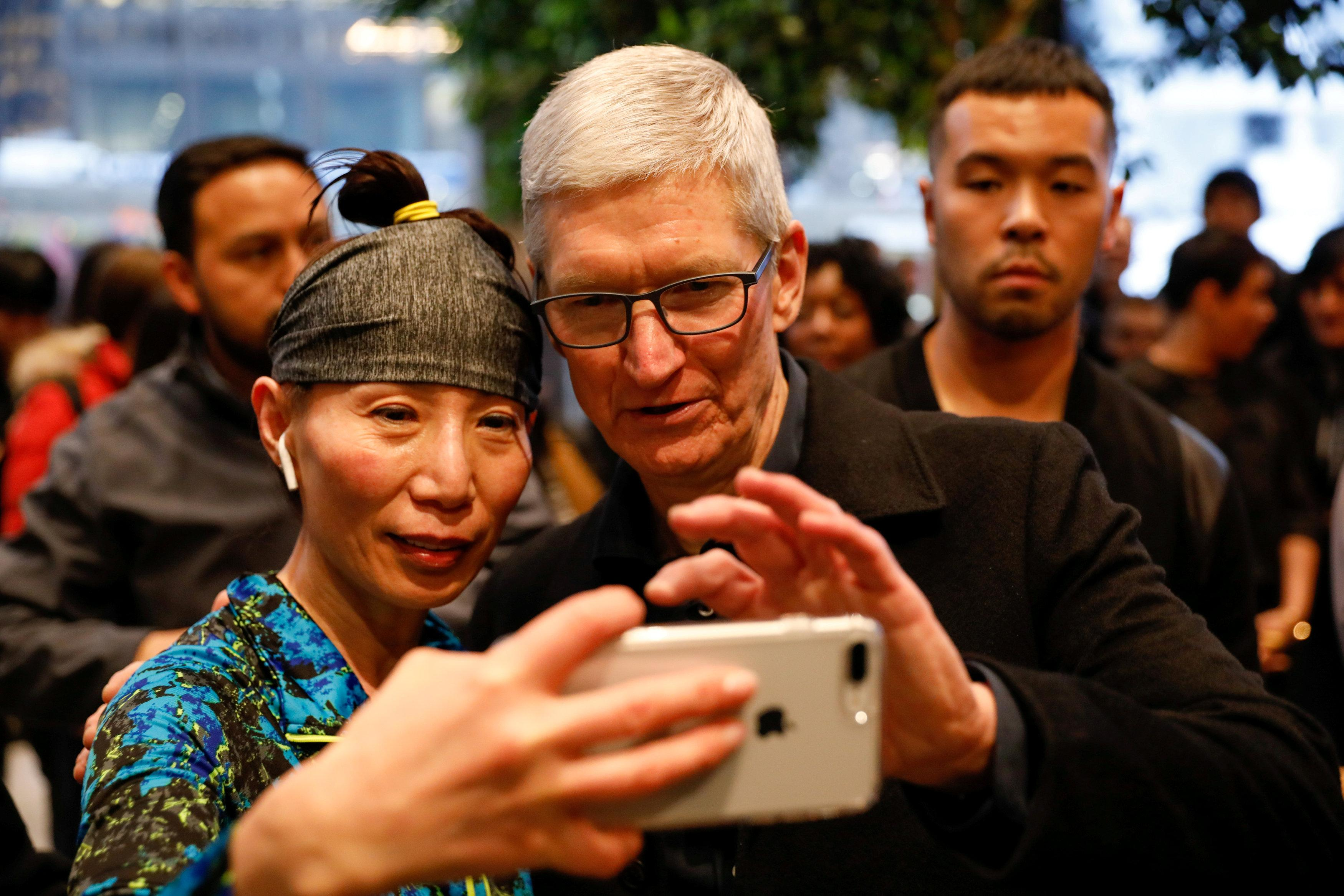 Tim Cook, Chief Executive Officer of Apple Inc., takes a selfie with a customer and her iPhone as he visits the Apple Store in Chicago, Illinois, U.S., March 27, 2018.   John Gress