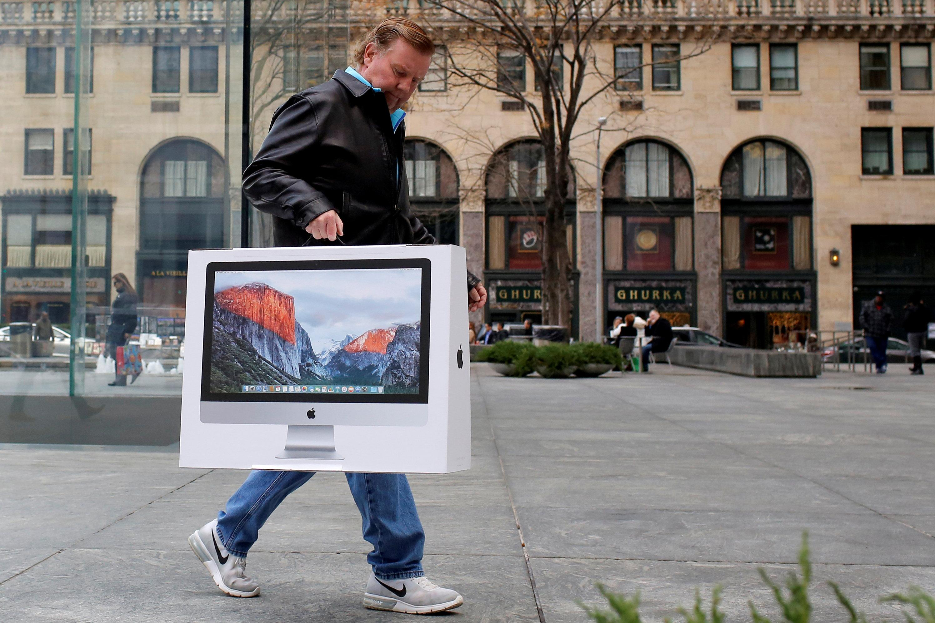 A man carries a newly purchased iMac from the Apple Fifth Avenue store during Black Friday sales in Manhattan, New York, U.S., November 25, 2016.  Andrew Kelly
