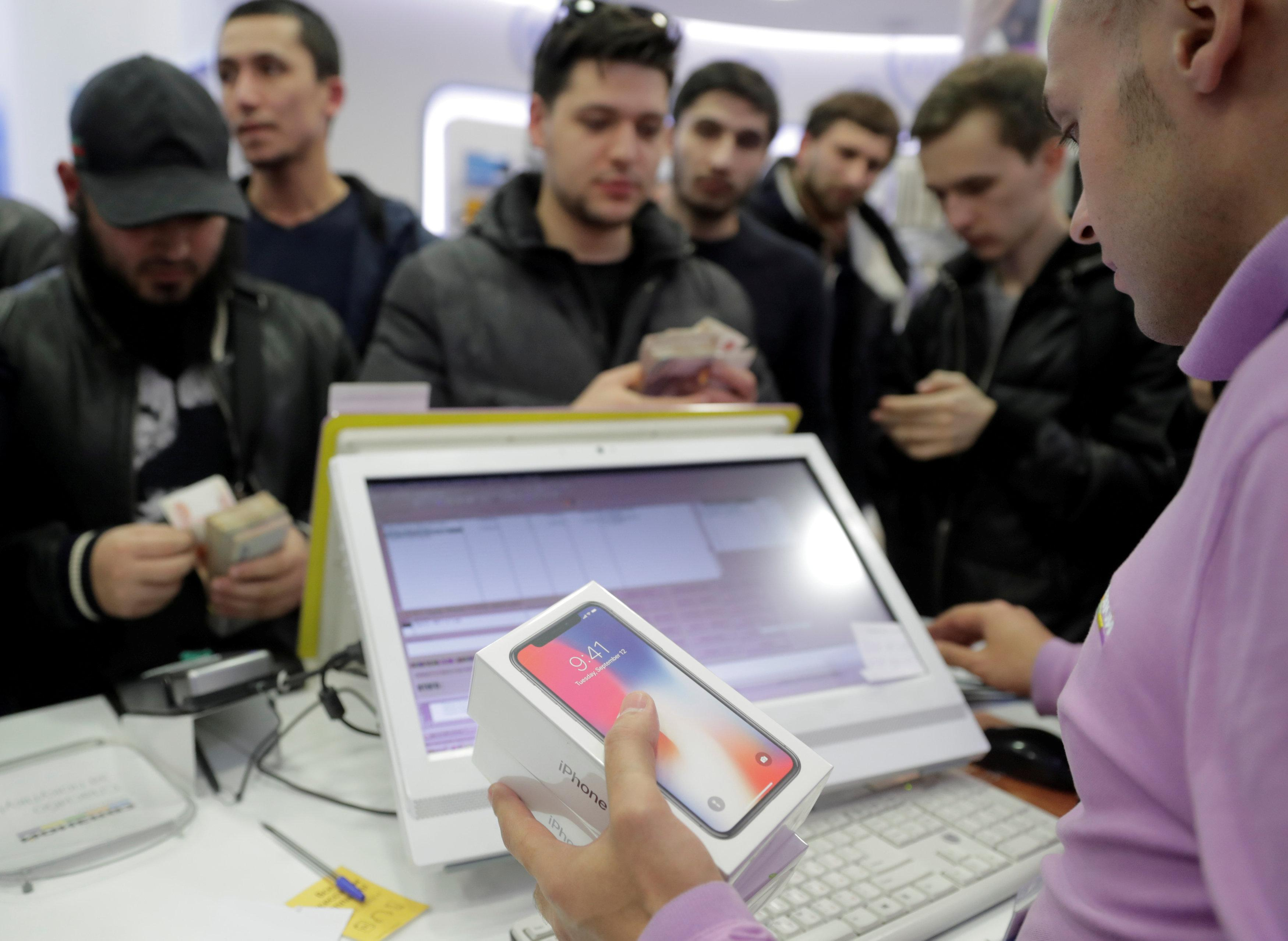 A store employee sells Apple's new iPhone X to first customers during its global launch at a cell phone store in central Moscow, Russia November 3, 2017. Tatyana Makeyeva