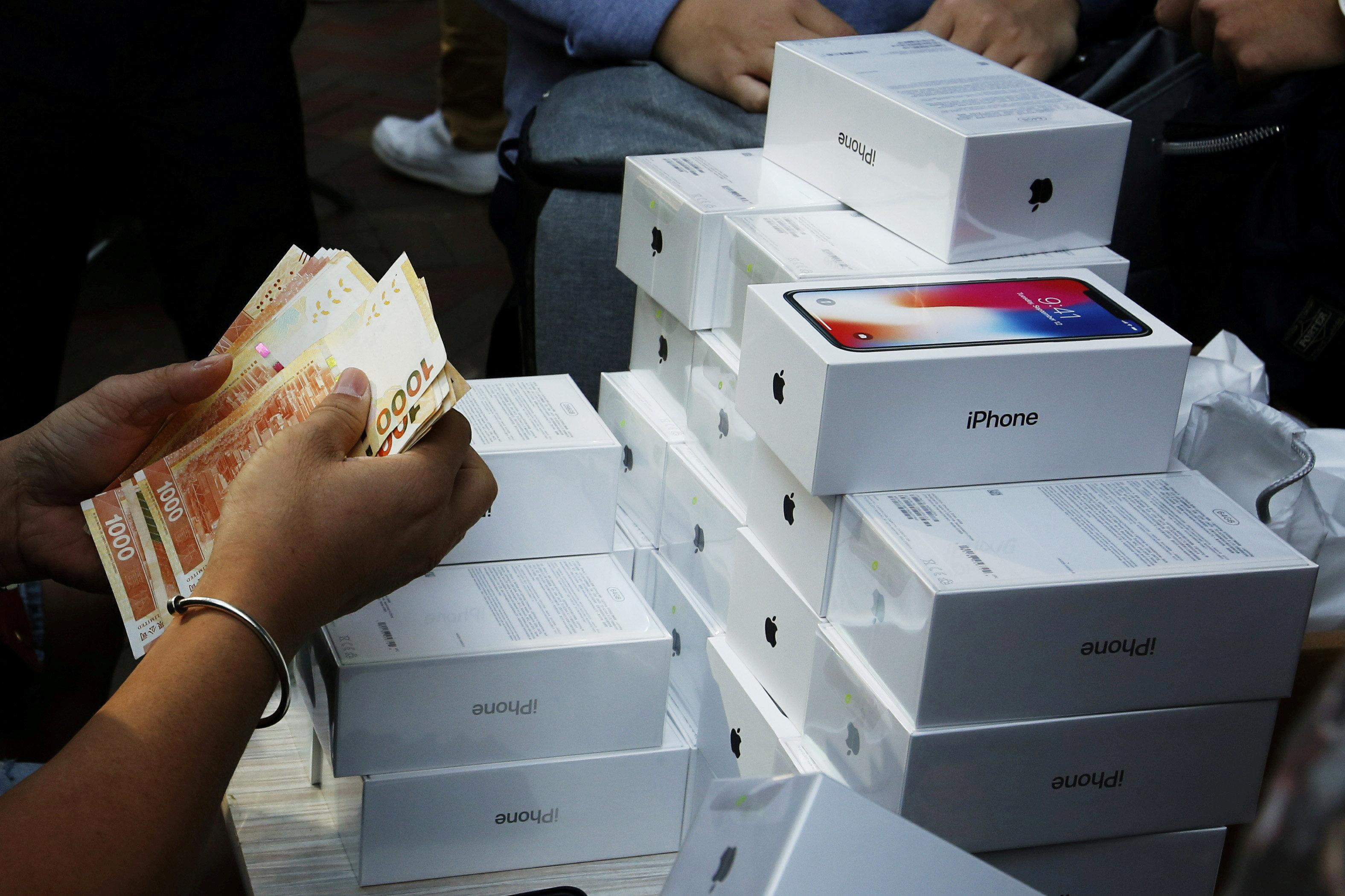 A man pays to buy new iPhone Xs from those who just bought at Apple Stores, on a street in Hong Kong, China November 3, 2017.  Bobby Yip