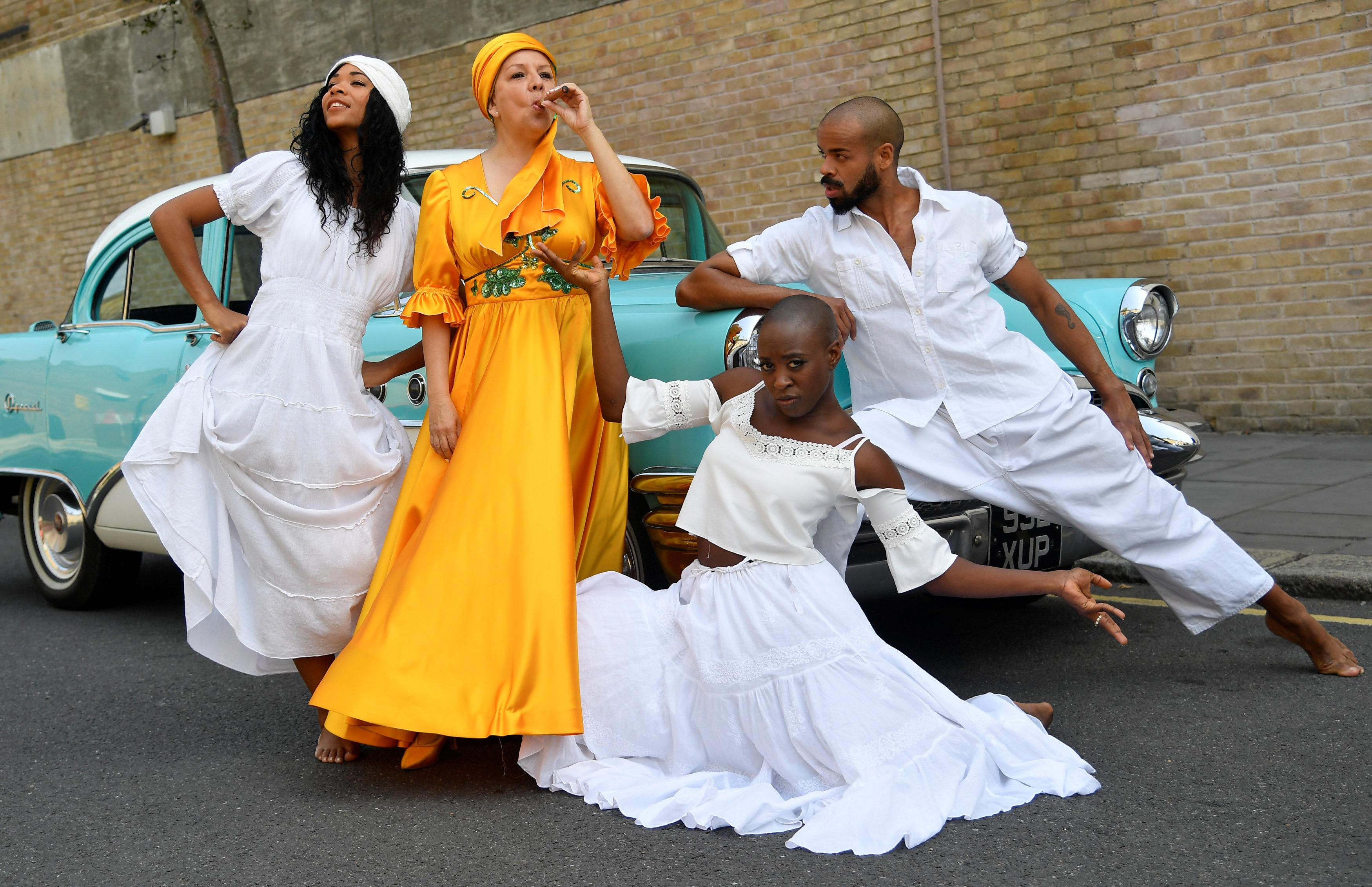 Cuban singer Albita Rodriguez (2L) stands with Cuban dancers (L to R) Yuyu Vega, Katia Aisler and Alejandro Aly beside a Buick Century classic car as the Grammy-award winning performer stars in the musical