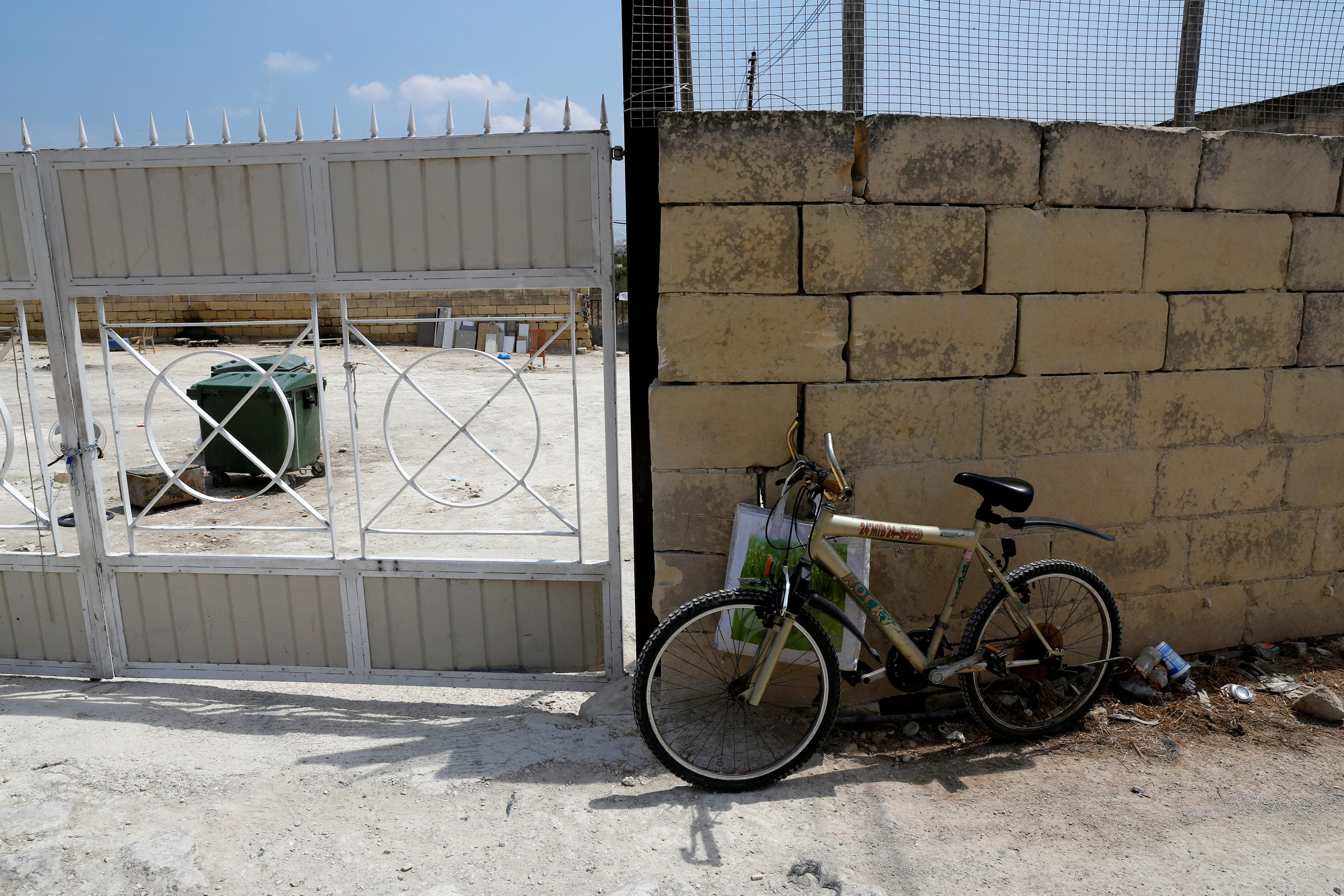 A migrant's bicycle is seen outside a farm where police evicted some 110 African migrants who had been living in stalls formerly used by cows, in Qormi, Malta August 13, 2018.  Darrin Zammit Lupi
