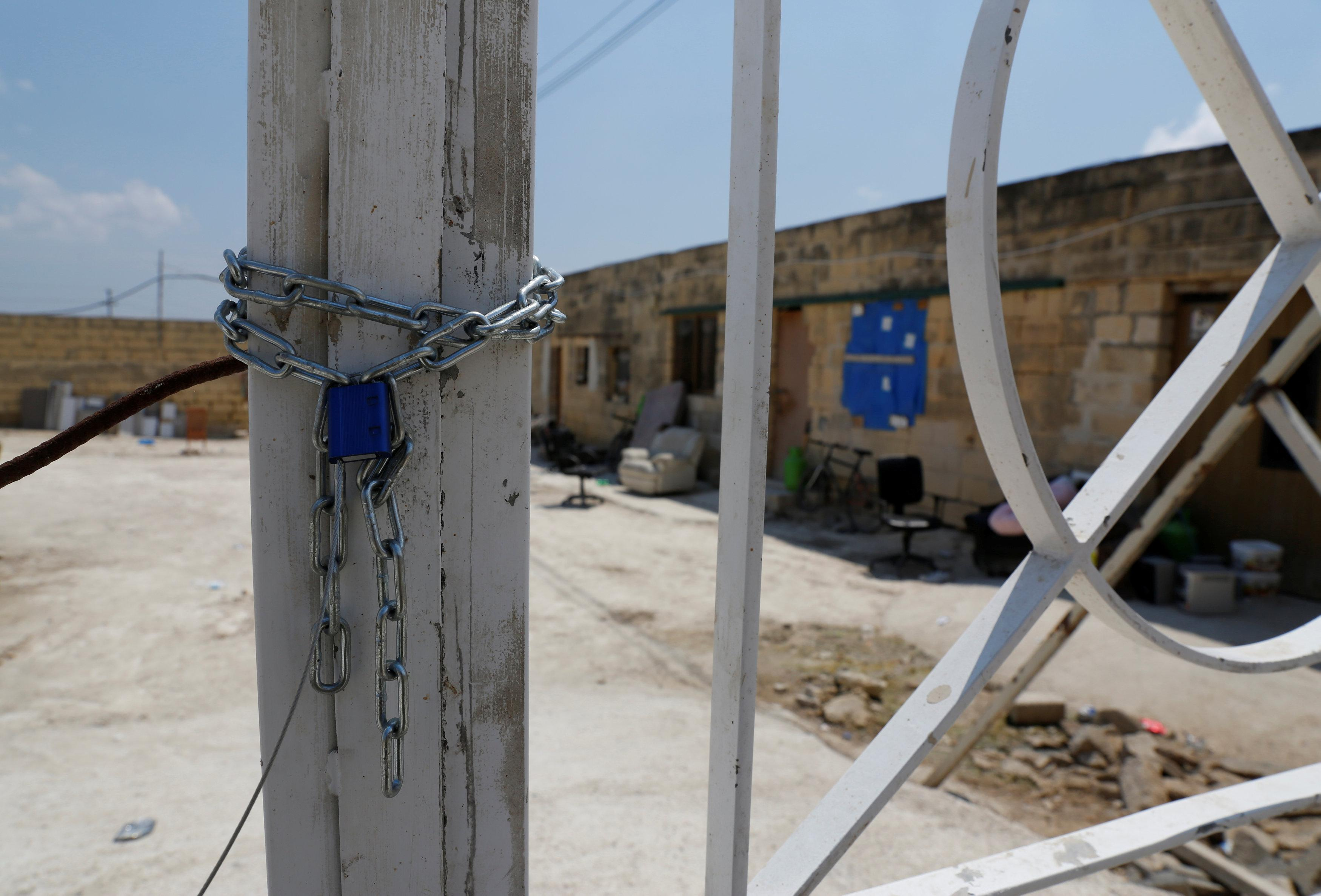The sealed gate leading to a farm where police evicted some 110 African migrants who had been living in stalls formerly used by cows, is seen in Qormi, Malta August 13, 2018.  Darrin Zammit Lupi