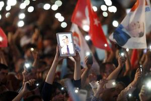 A supporters displays a picture of Turkey's Prime Minister Erdogan on a...