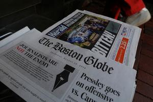 The front page of the Boston Globe newspaper references their editorial...