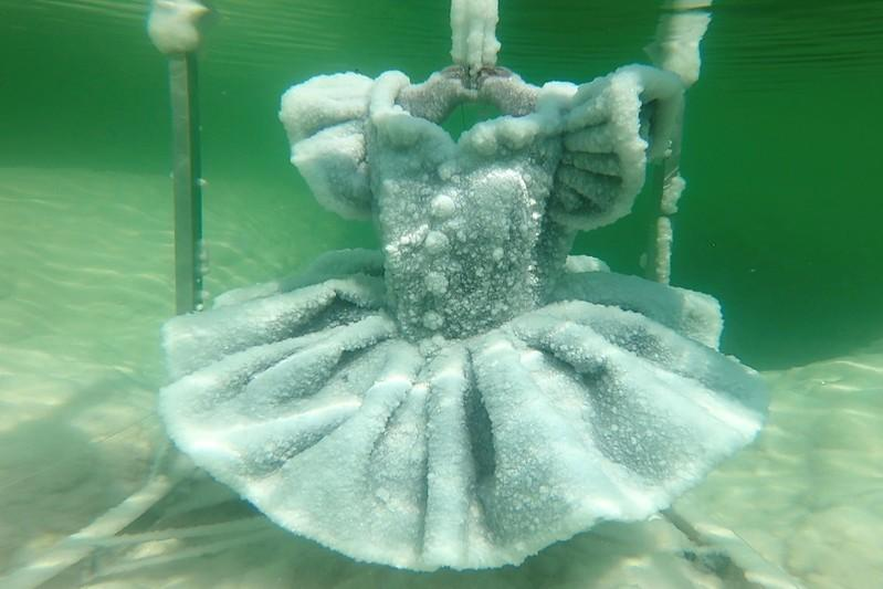 One of Israeli artist Sigalit Landau's pieces, a ballerina's tutu covered in salt crystal formations, is seen submerged in the hyper-saline waters of the Dead Sea, Israel August 30, 2018, in this still image taken from a video.  TV/ via