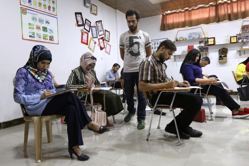 Iraqi students take an English language exam at a bookstore in Kirkuk, Iraq, July 24, 2018. Ako Rasheed