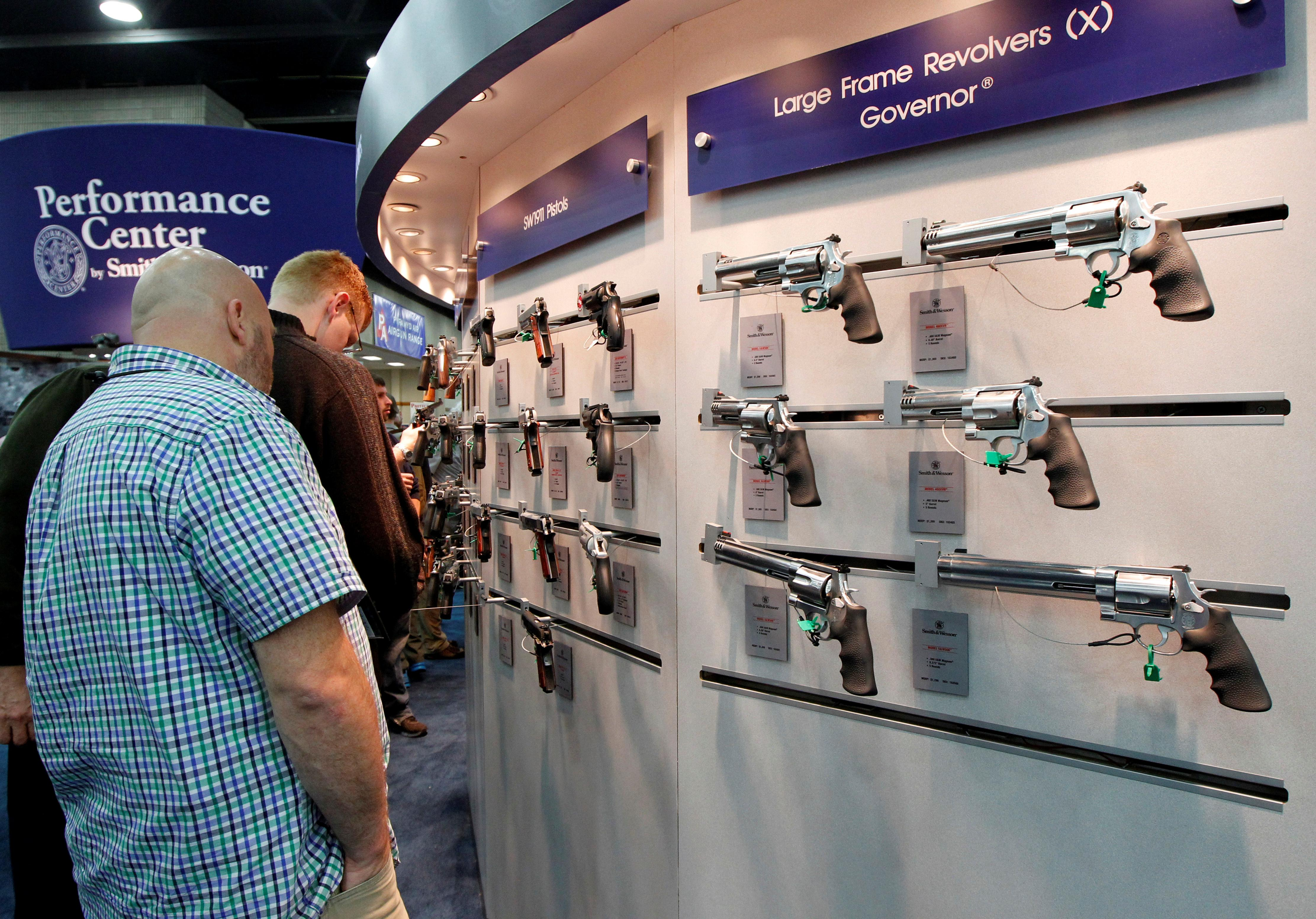Gun enthusiasts look over Smith & Wesson guns at the National Rifle Association's (NRA) annual meetings and exhibits show in Louisville, Kentucky, May 21, 2016.   John Sommers II